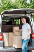 happy young man standing near car trunk with boxes for relocation into new house