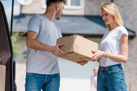 Photo for Man giving cardboard box to wife while their daughter standing behind in yard of new house - Royalty Free Image