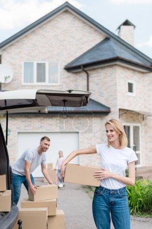 Photo pour Couple souriant porte des boîtes en carton pour déménagement dans la nouvelle maison et de leur fille à cheval sur kick scooter derrière - image libre de droit