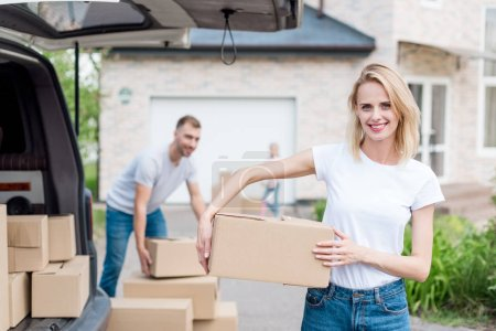 smiling woman holding cardboard box for relocation into new house and her husband and daughter standing behind in front of new house