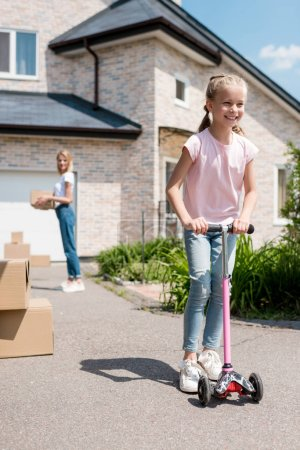 smiling little child riding on kick scooter while her mother unpacking cardboard boxes in front of new house