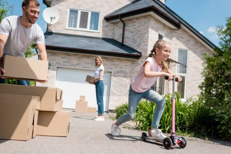 little kid riding on kick scooter and her parents unpacking cardboard boxes for relocation into new house