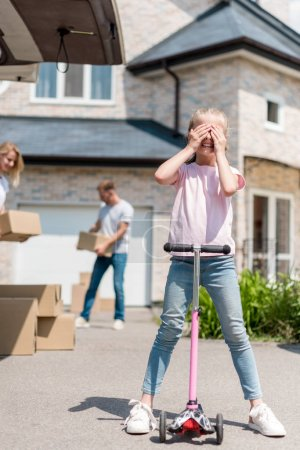 little kid covering eyes on kick scooter and her parents unpacking cardboard boxes for relocation into new house