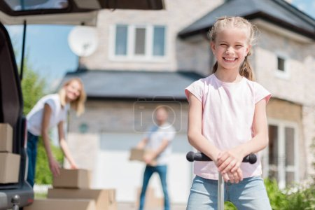 smiling little kid on kick scooter and her parents unpacking cardboard boxes for relocation into new house