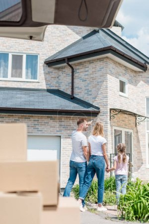 back view of man pointing by finger at new house to wife and daughter