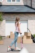 back view of kid riding on kick scooter near boxes and acoustic guitar in front of new house