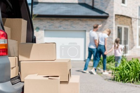 closeup view of cardboard boxes and family holding hands and walking behind in yard of new house