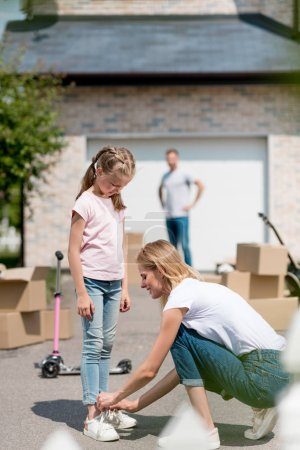 side view of smiling woman tying shoelaces of daughter and man standing behind near cardboard boxes in yard of new cottage