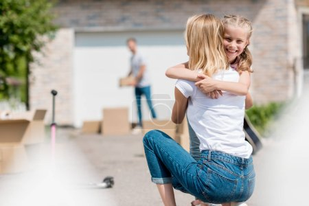 rear view of woman hugging smiling daughter and man unpacking cardboard boxes behind in yard of new house