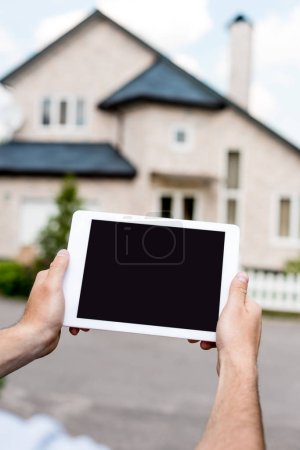 cropped shot of man holding digital tablet with blank screen in front of cottage