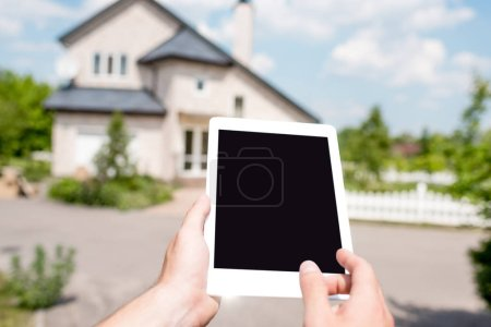 cropped image of man holding digital tablet with blank screen in front of cottage