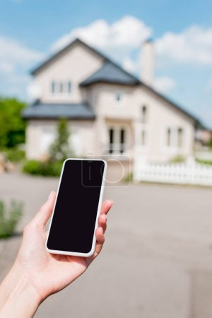 cropped shot of young woman holding smartphone with blank screen in front of house
