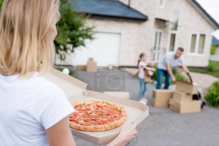 partial view of  woman holding pizza while her husband and daughter unpacking cardboard boxes in front of new house