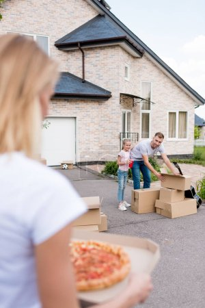 cropped image of woman holding pizza while her husband and daughter unpacking cardboard boxes in front of new house