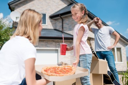 side view of happy mother holding box with pizza and daughter with cup of cola taking slice of pizza while father standing behind of new house