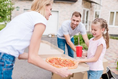 Photo for Smiling mother holding box with pizza and daughter taking slice of pizza while father unpacking cardboard boxes - Royalty Free Image