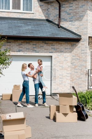 front view of happy couple standing with daughter on hands in front of new house