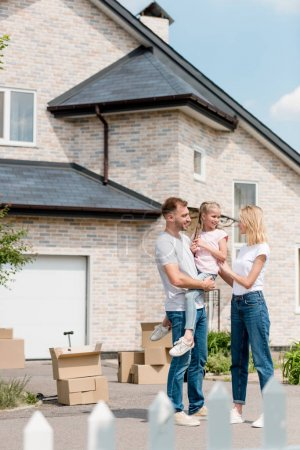 couple standing with daughter on hands in front of new house