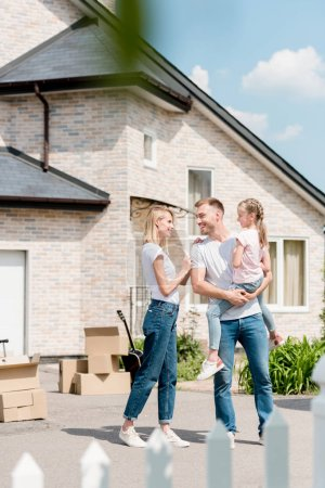 attractive woman embracing smiling husband while he holding daughter inf front of new house
