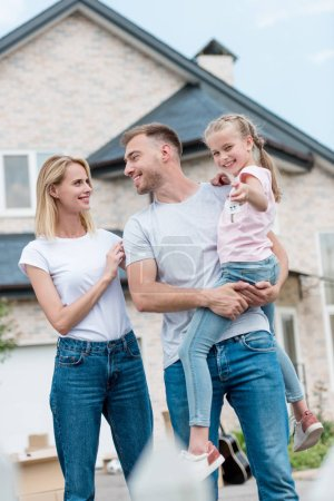 woman embracing husband while he holding daughter inf front of new house