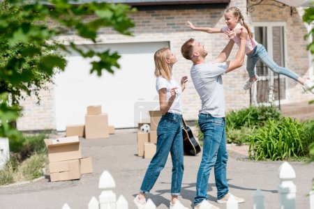 father raising up daughter while mother standing near in front of their new house