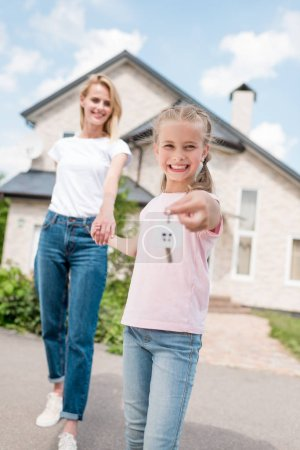 happy smiling kid showing key with trinket and holding hand of mother in front of new house