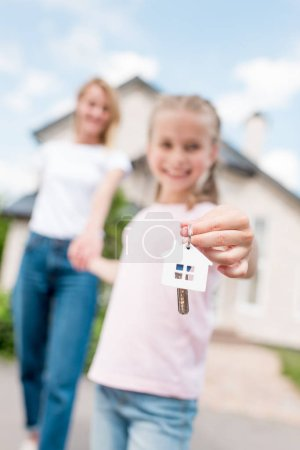 closeup shot of smiling kid showing key with trinket and holding hand of mother