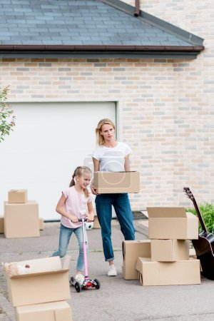 mother unpacking cardboard boxes and little daughter riding on kick scooter in front of new cottage