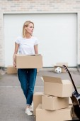 attractive woman with cardboard box moving into new house