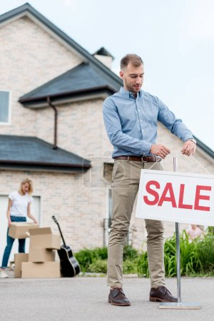 male realtor hanging sale sign in front of woman packing cardboard boxes for relocating from house