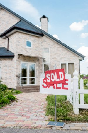 sold sign on wooden placard with sale sign in front of modern cottage