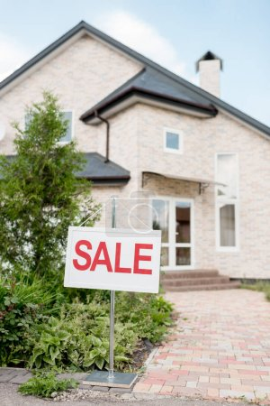 wooden placard with sale sign in front of modern cottage