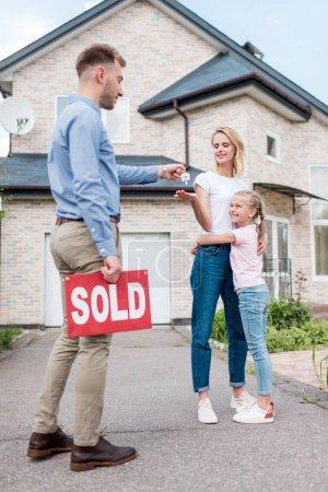 Photo pour Agent immobilier avec signe vendu donnant la clé à une jeune femme avec sa fille devant une nouvelle maison - image libre de droit