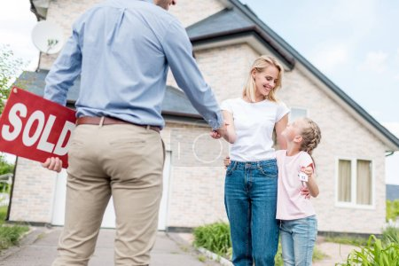 woman with daughter buying new house and shaking hand of male realtor with sold sign in hand