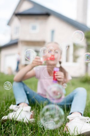 little child with soap bubbles sitting on lawn while her mother standing behind in front of house