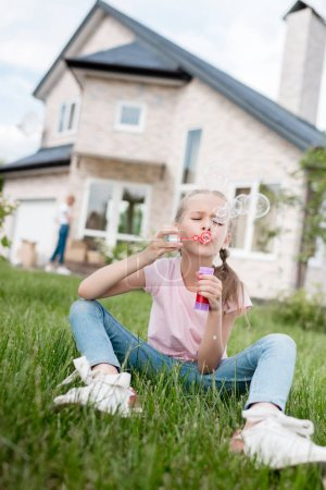 little kid using bubble blower and sitting on lawn while her mother standing behind in front of house