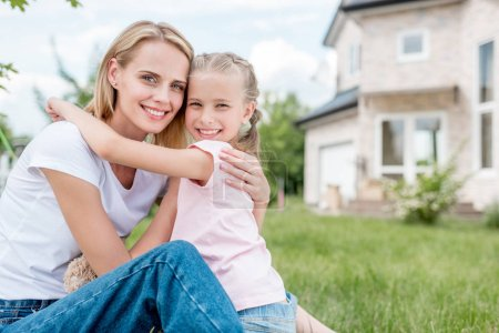 happy little child embracing smiling mother on green lawn