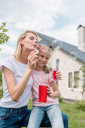 young woman blowing soap bubbles while her daughter sitting near with cup of cola