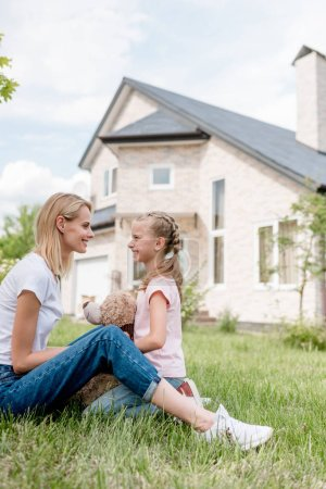 side view of smiling mother looking at daughter with teddy bear sitting on lawn in front of house