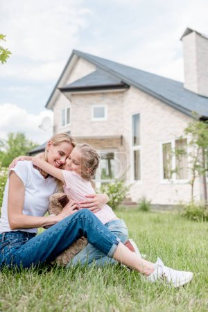 little daughter hugging smiling mother on green lawn in front of cottage