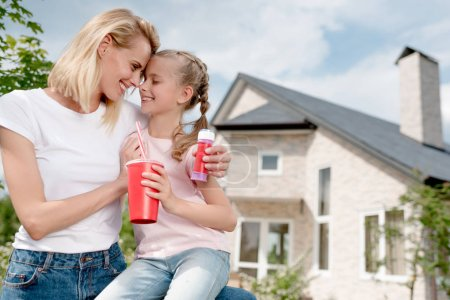 happy woman sitting forehead to forehead with daughter and holding bubble blower in front of new house