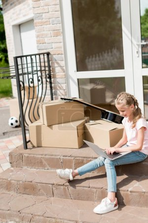little kid using laptop near boxes and guitar on stairs near new cottage
