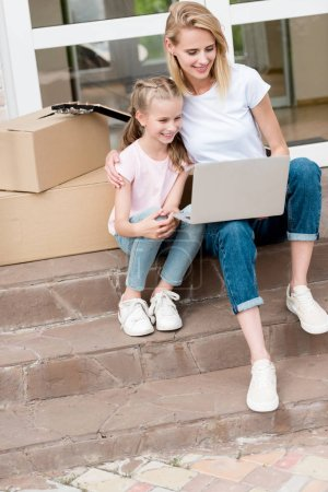 happy woman with daughter using laptop on stairs with cardboard boxes and guitar in front of new house