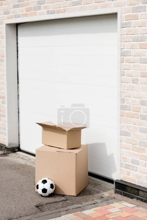 close up shot of boxes, soccer ball in front of garage gate