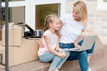 smiling woman with daughter using laptop on stairs with cardboard boxes and guitar in front of new house
