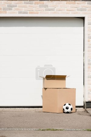 close up view of boxes, soccer ball in front of garage gate