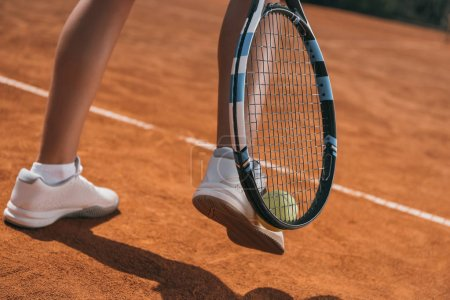 Photo for Cropped shot of woman picking up tennis ball with racket and leg - Royalty Free Image