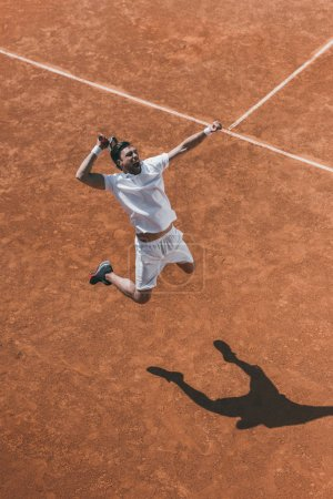 Photo for High angle view of young tennis player making hit in jump - Royalty Free Image