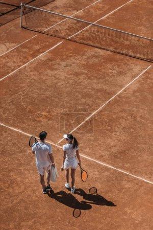 Photo pour Vue d'angle élevé de couple sportive avec des raquettes, à pied par un court de tennis - image libre de droit