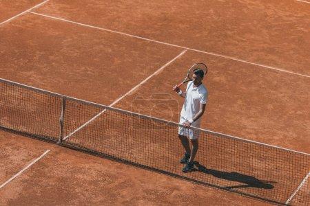 Photo pour Vue grand angle de l'homme au repos sur un court de tennis, après match - image libre de droit